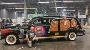 Carlos con vehículo fúnebre